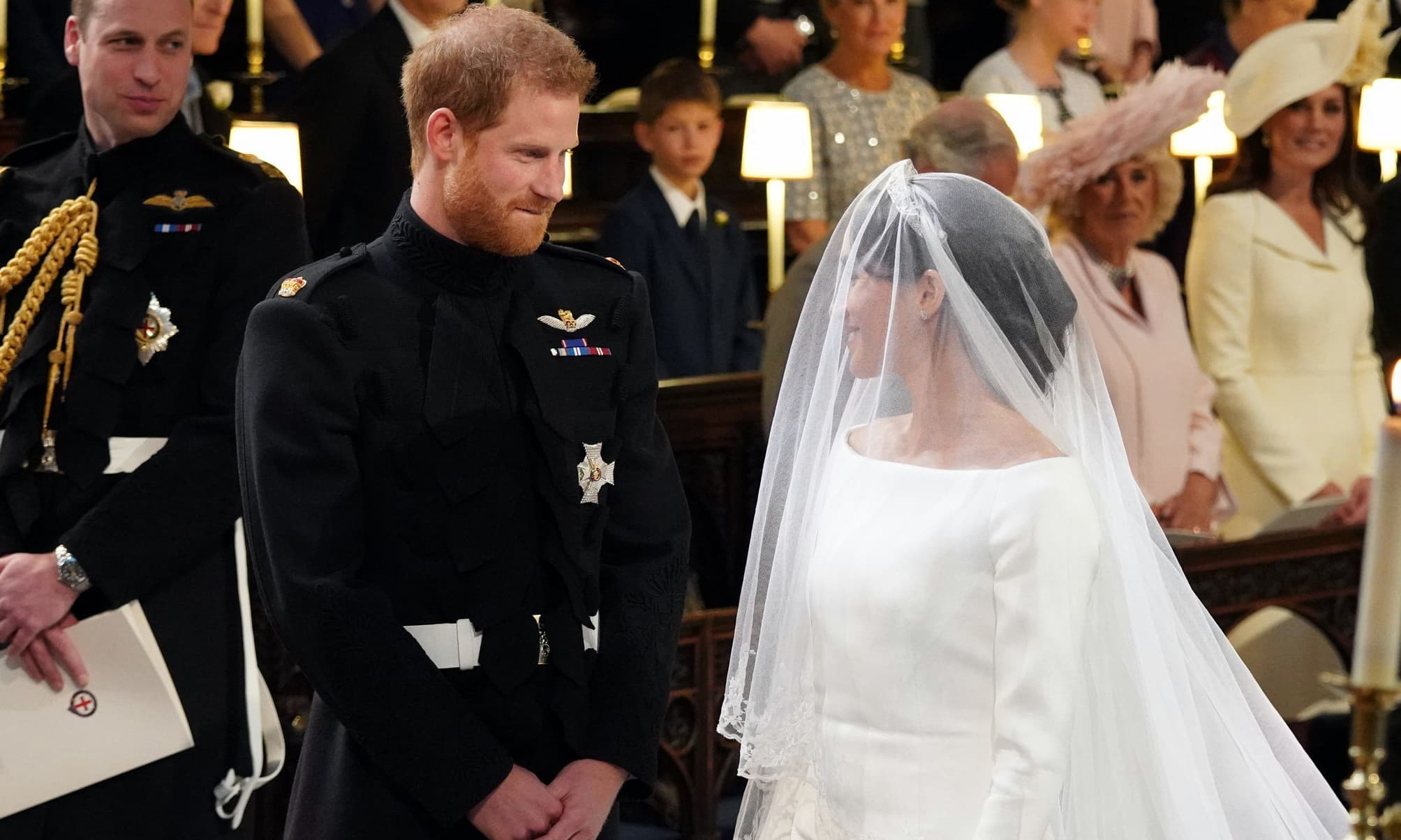 Britain's Prince Harry looks at his bride, Meghan Markle, during their wedding ceremony at St. George's Chapel. — AP