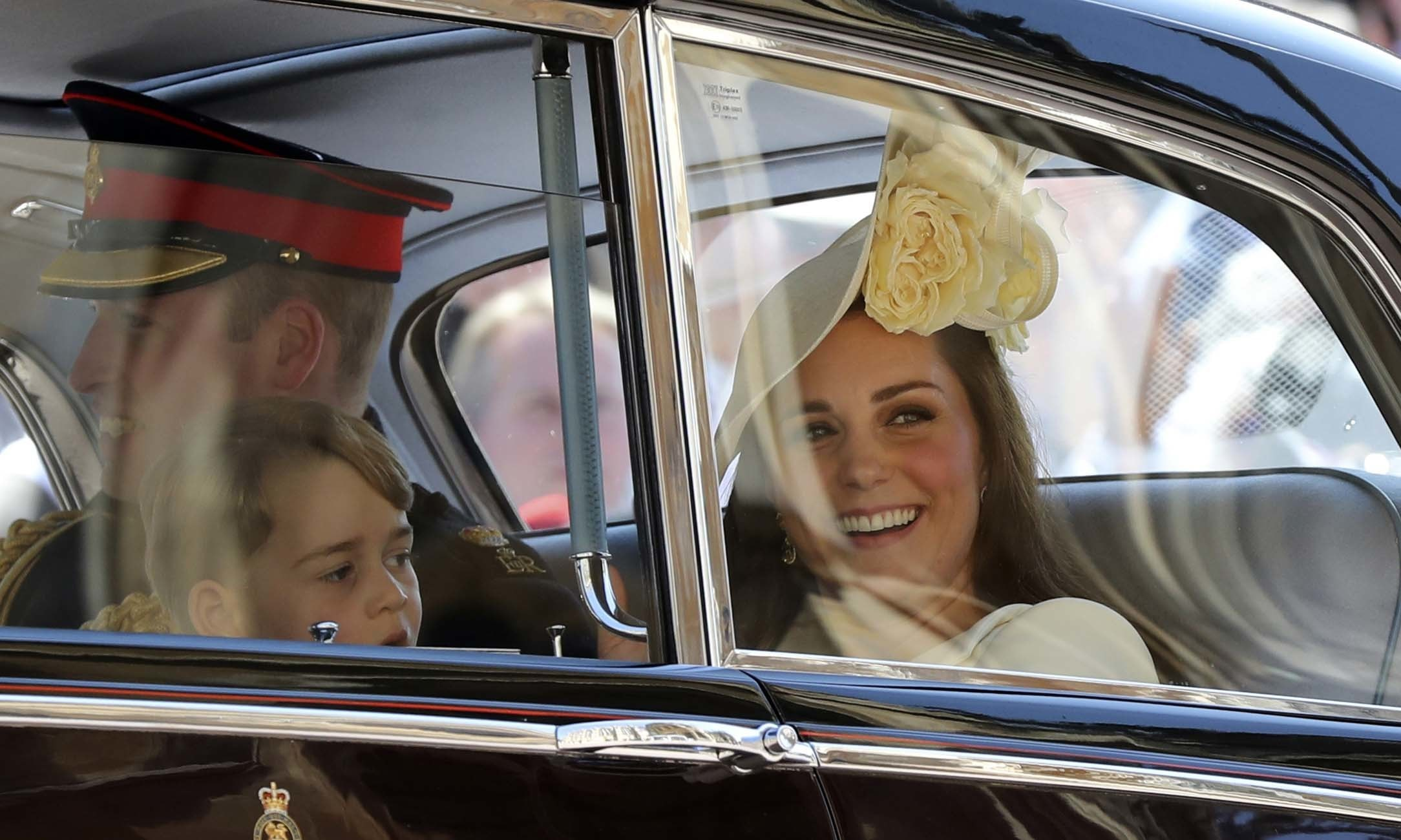 Prince George looks on as the Duchess of Cambridge smiles at the crowd outside — AP