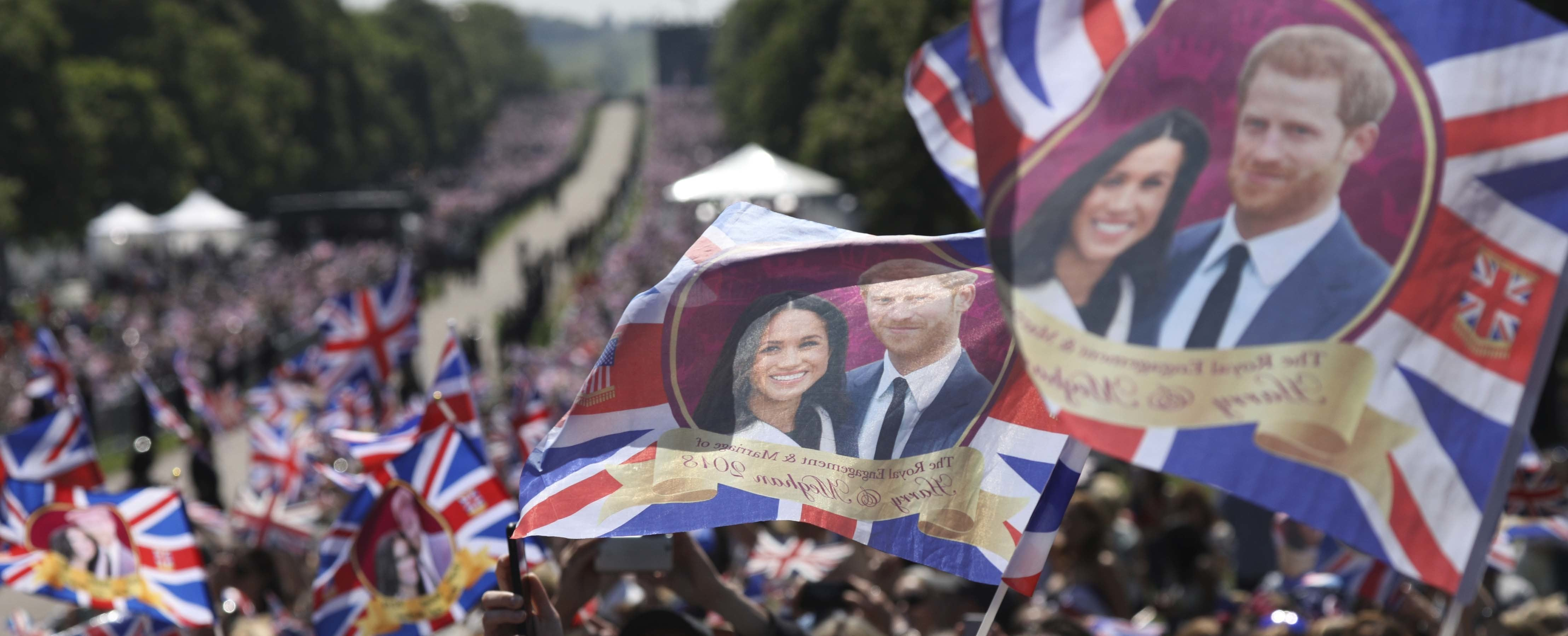 Royal fans wave flags with when waiting for the newlyweds to go past after the wedding ceremony of Prince Harry and Meghan Markle at St. George's Chapel in Windsor Castle in Windsor, near London, England, Saturday, May 19, 2018. (AP Photo/Emilio Morenatti) — Copyright 2018 The Associated Press. All rights reserved.