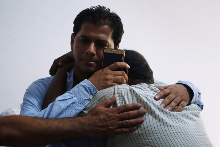 Aziz Sheikh (left), father of Sabika Aziz Sheikh, is comforted by a relative at his residence in Karachi. —Reuters/File