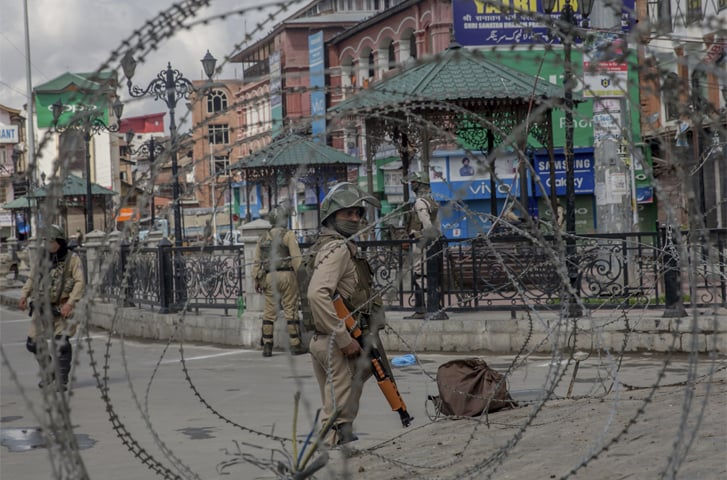 paramilitary soldiers are seen through barbed wire in Srinagar on Saturday.—AP