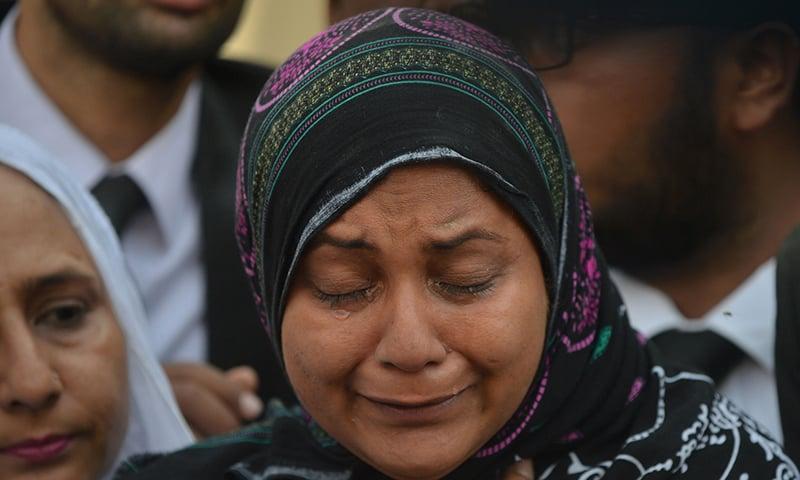 Asma Nawab weeps before entering her house after her release in Karachi. —AFP