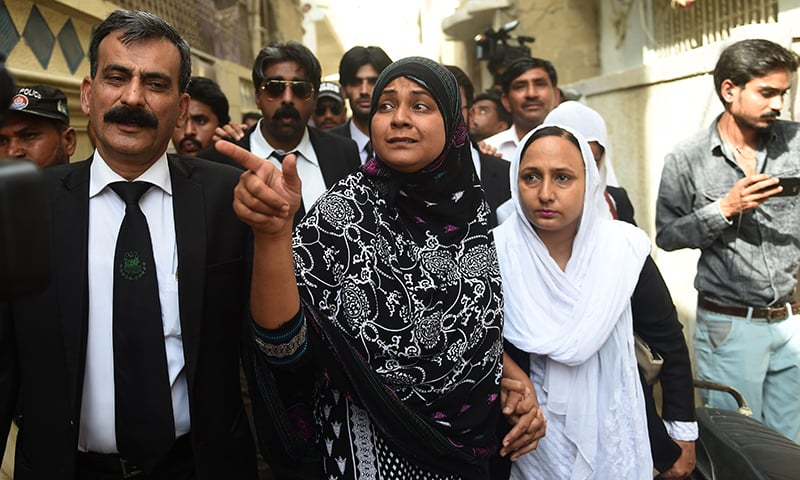 Asma Nawab (C) gestures before entering her house alongside her lawyer Javed Chatari (L) after her release in Karachi. —AFP