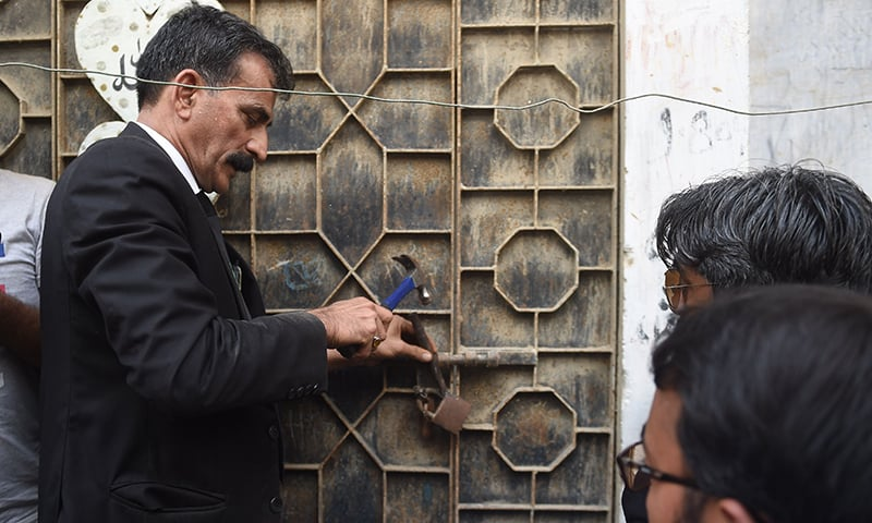 Lawyer Javed Chatari breaks the gate's lock at Asma Nawab's house. —AFP