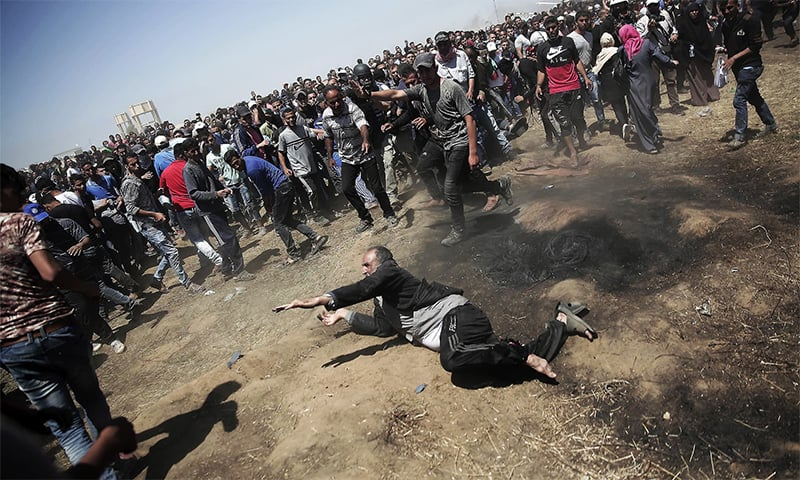 An elderly Palestinian man falls on the ground after being shot by Israeli troops during a deadly protest at the Gaza Strip's border with Israel, east of Khan Younis, on Monday, May 14, 2018. — AP