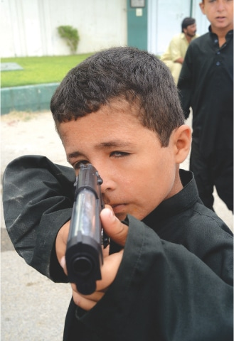 A child playfully points a toy gun | Tahir Jamal / White Star