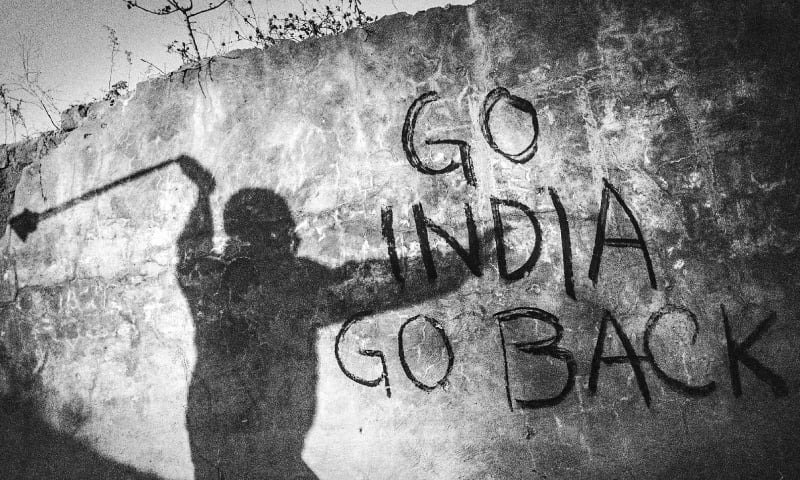 The shadow of a Kashmiri protestor throwing stones at Indian soldiers on a wall marked with an anti-India graffiti. The year 2010 proved to be the bloodiest year in the history of anti-India protests in Kashmir
