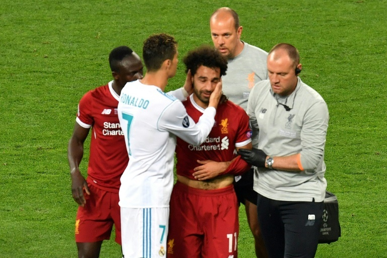 Salah is comforted by team-mates and opponents alike after injury forces him off in the final. ─ AFP