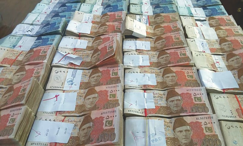 LAHORE: Stacks of currency notes that were seized in a NAB raid on the car showroom on Monday.—Dawn
