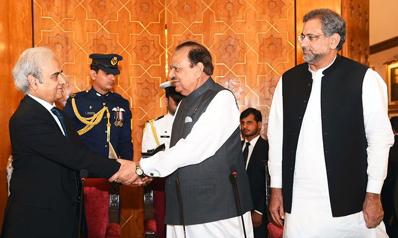 This handout photograph released by the Press Information Department shows President Mamnoon Hussain greeting the caretaker Prime Minister Nasir-ul-Mulk (L) as outgoing prime minister Shahid Khaqan Abbasi looks on during an oath-taking ceremony at The President House in Islamabad. — AFP