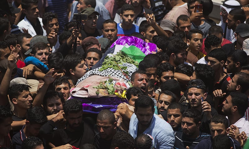 Palestinian mourners carry the body of a volunteer paramedic Razan Najjar, 21, during her funeral in town of Khan Younis, Southern Gaza Strip. — AP