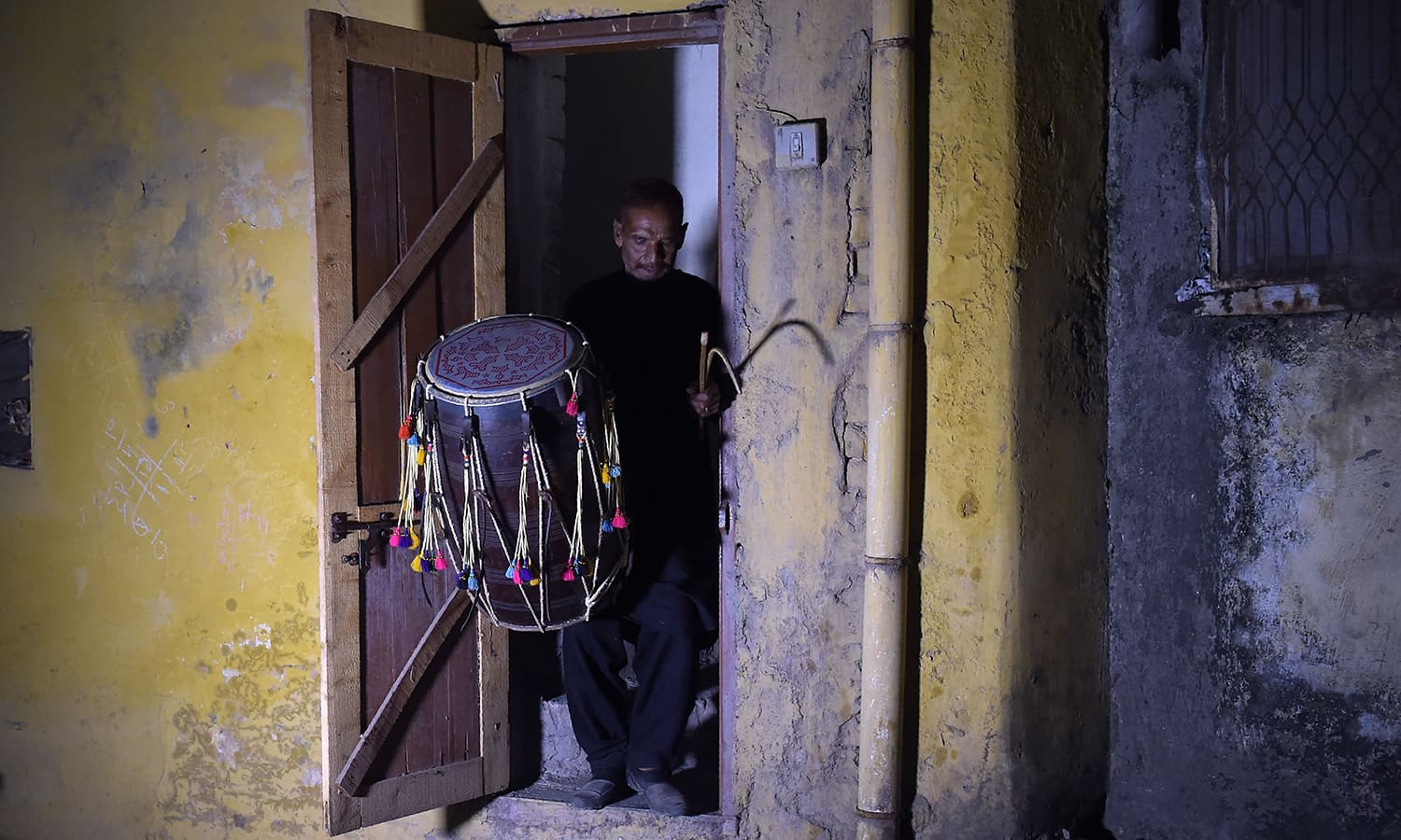 Lal Hussain, 66, 'Ramazan drummer' holds his drum as he leaves his house to makes calls at doors. — AFP