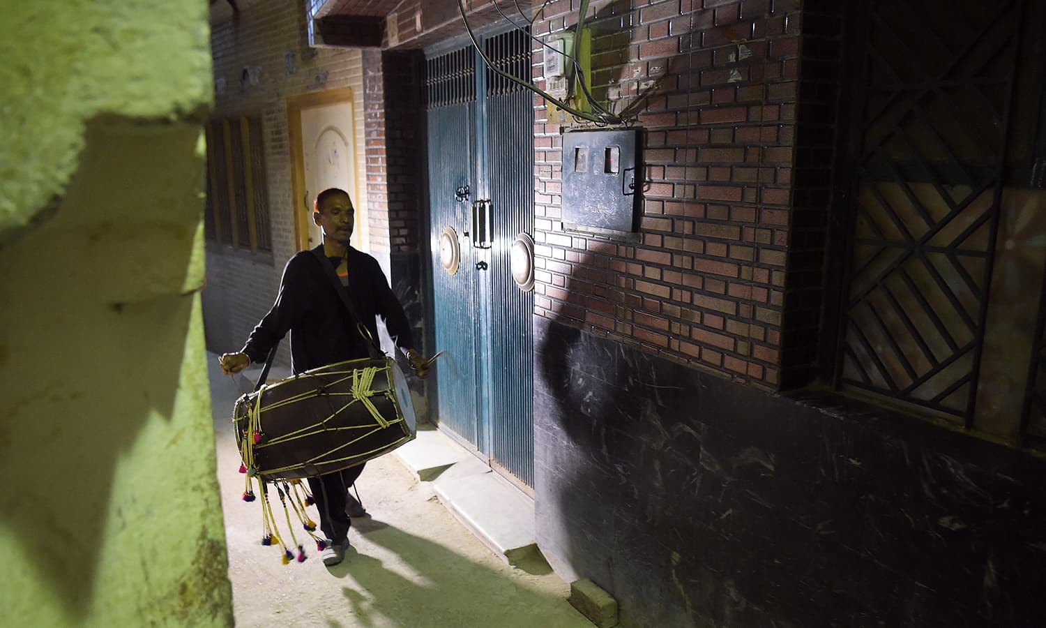 Lal Hussain roams on streets of a residential area, waking people up for sehri by his drum beats. — AFP