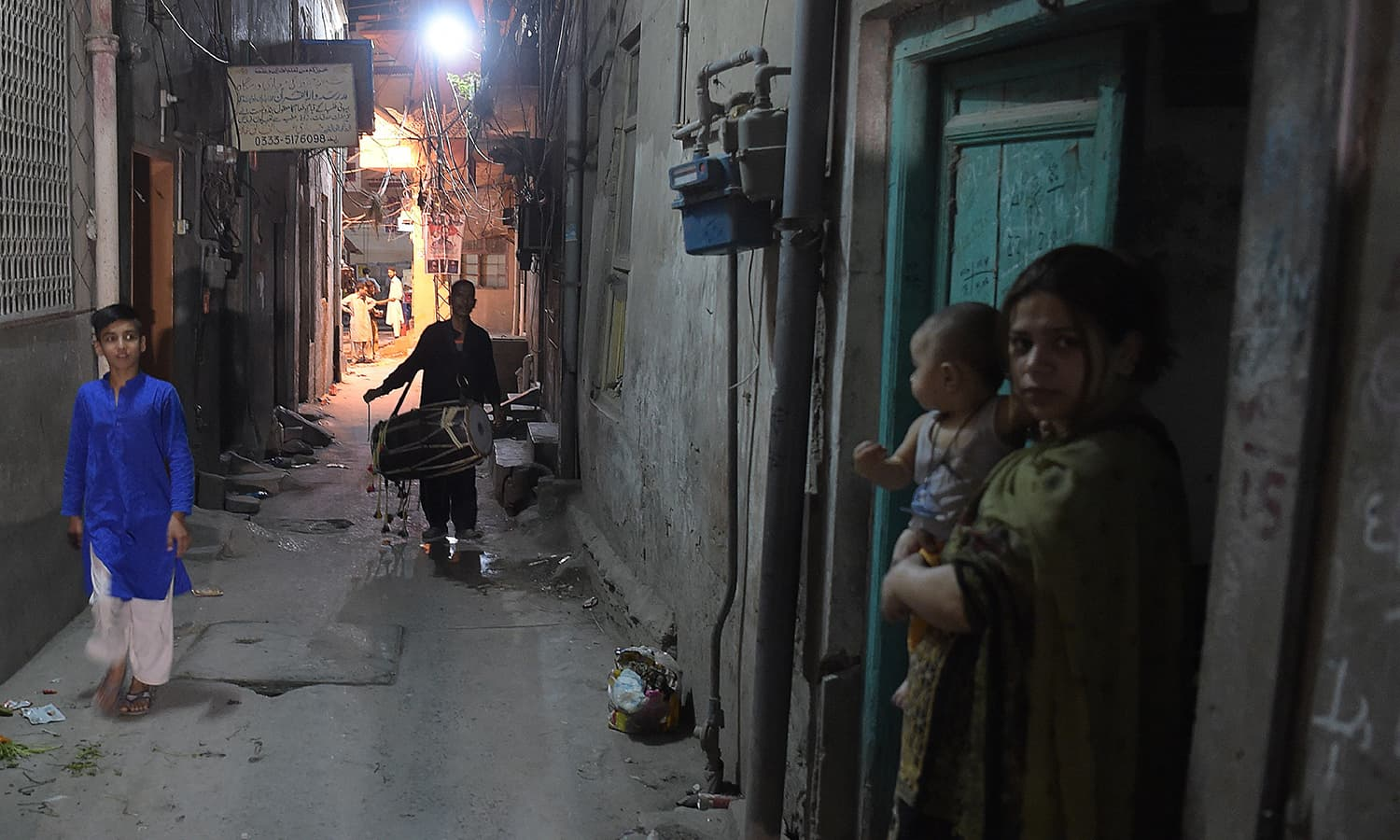 Residents of the area look on as Lal Hussain walks in streets, beating his drum to wake people up for sehri. — AFP