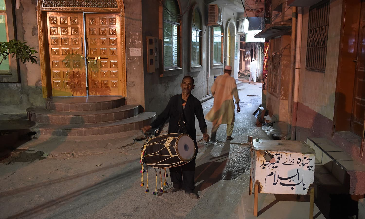 Lal Hussain walks around a residential area, beating his drum to wake people up for sehri. — AFP