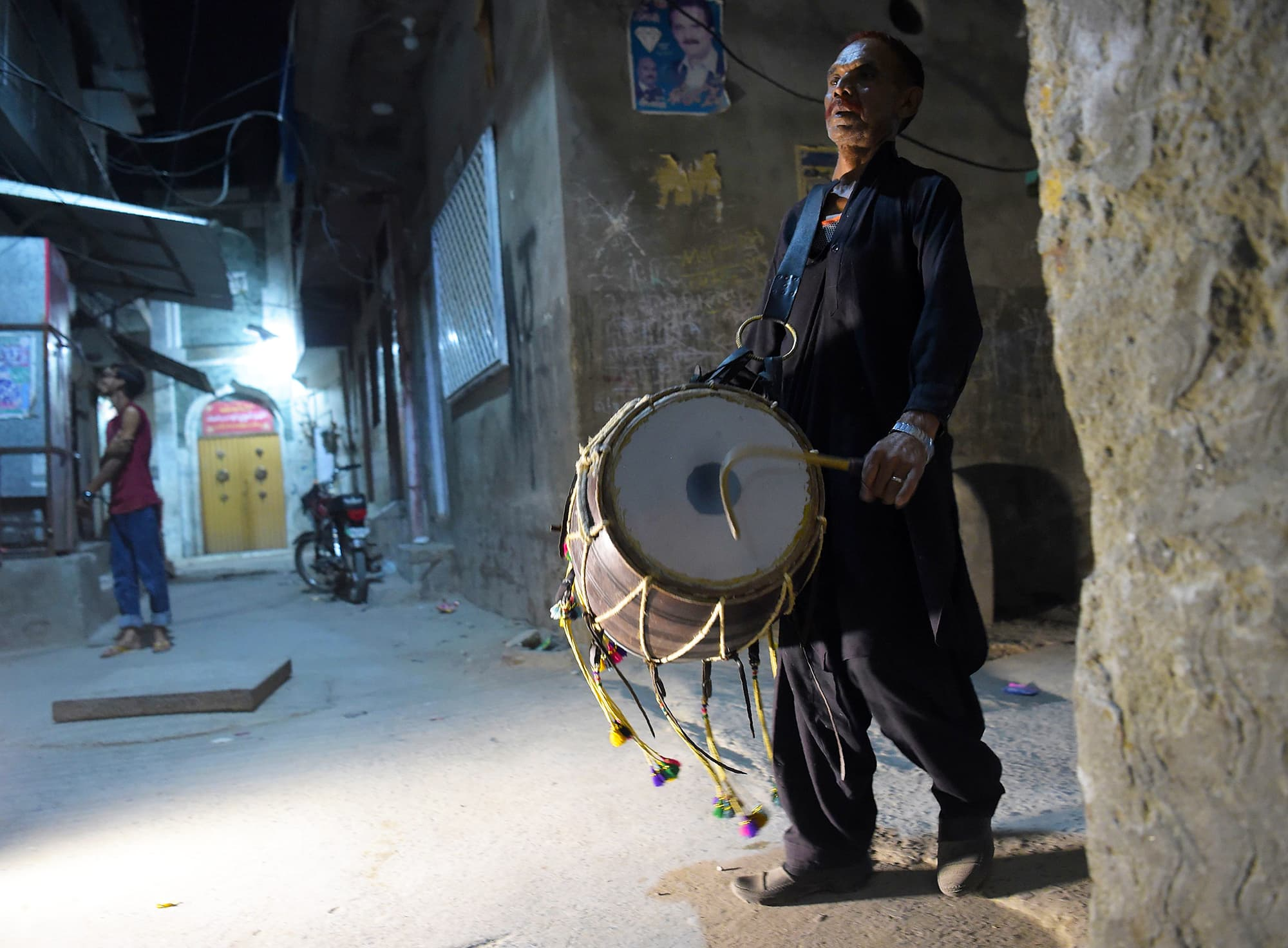 Lal Hussain, 66, beats his drum as he makes calls at doors to wake people up for Sehri by his drumbeats. — AFP