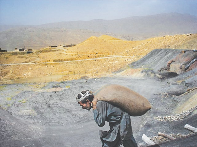 A miner hauls a sack of coal on his back; despite the toil and labour, miners opt for mining as a life-long profession | Photo by Mukhtar Azad