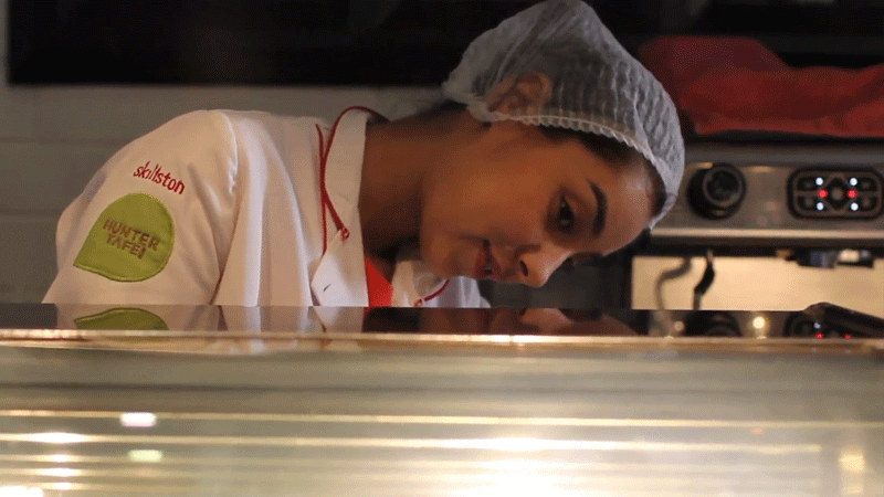 Arooj inspects the baked goods to see if they're fresh.