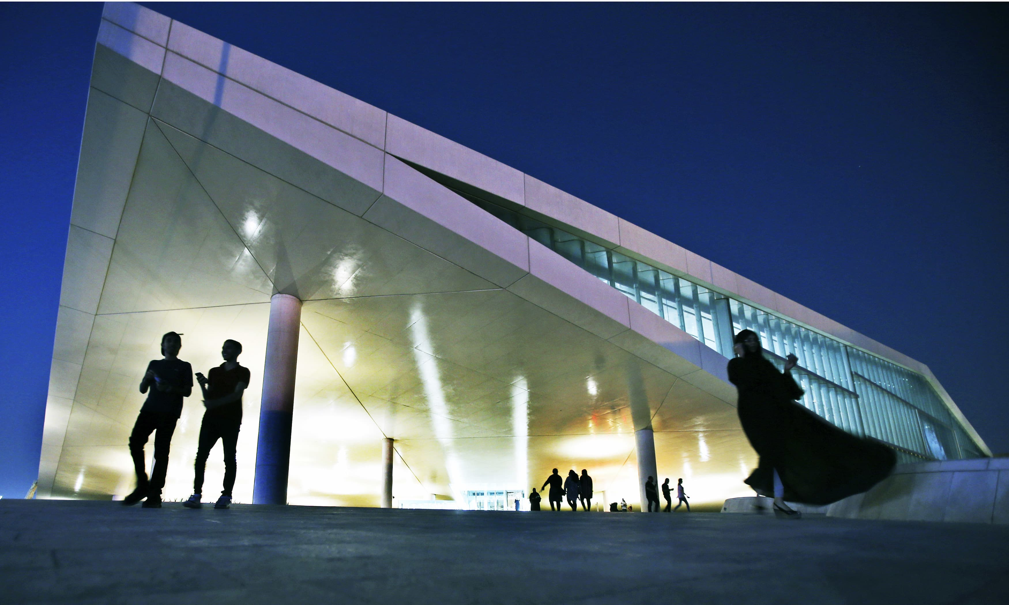 People leave the Qatar National Library building designed by Dutch architecture firm OMA and has opened recently in Doha, Qatar. —AP