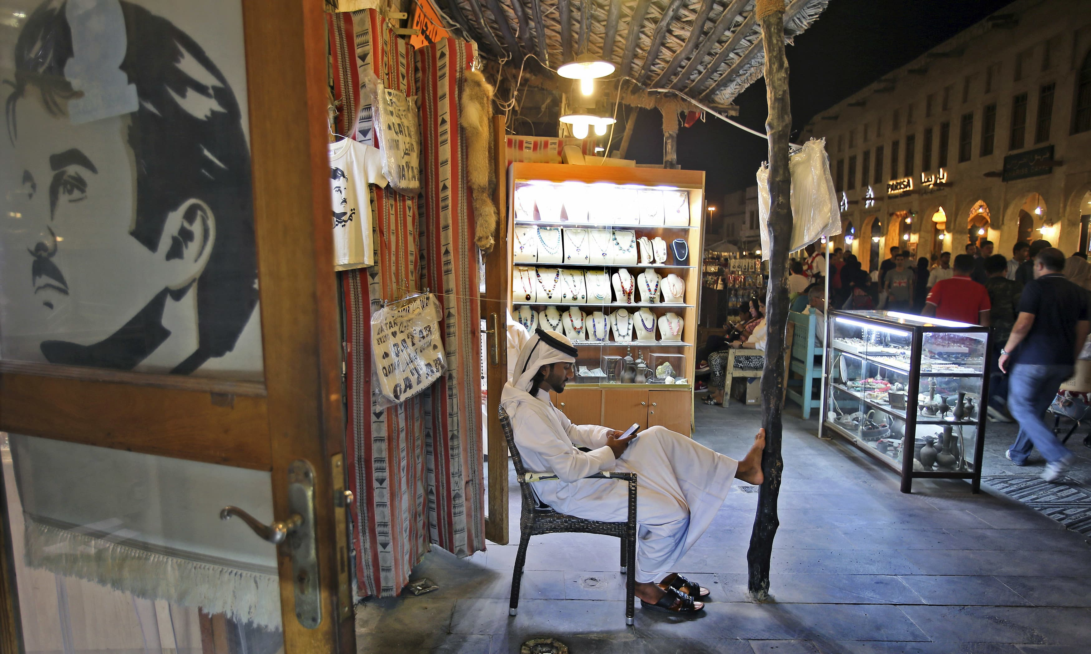 A poster of the Emir of Qatar Sheikh Tamim bin Hamad Al Thani is displayed on the door of a jewelry store in the Waqif Souq. —AP