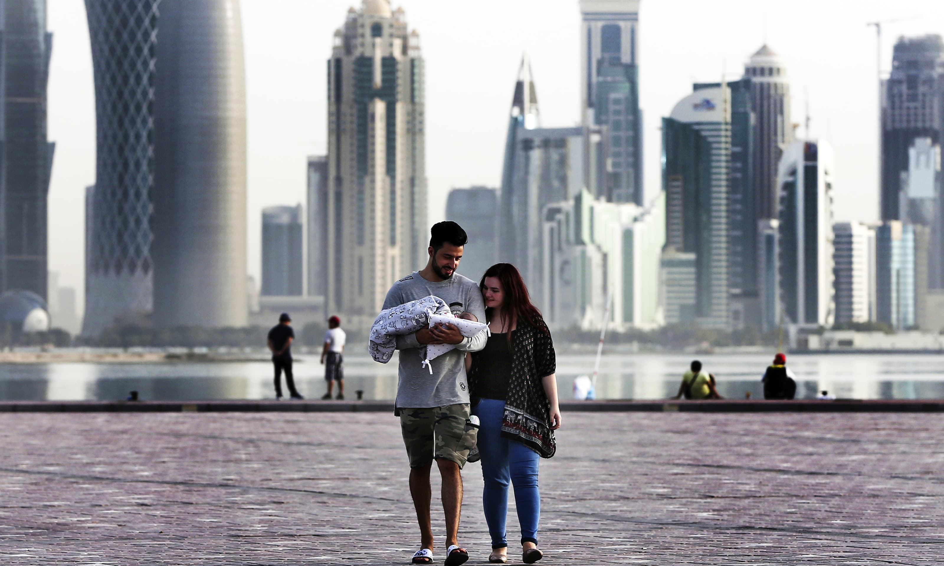 A couple take a weekend walk with their new born baby along the waterfront, in Doha, Qatar. —AP