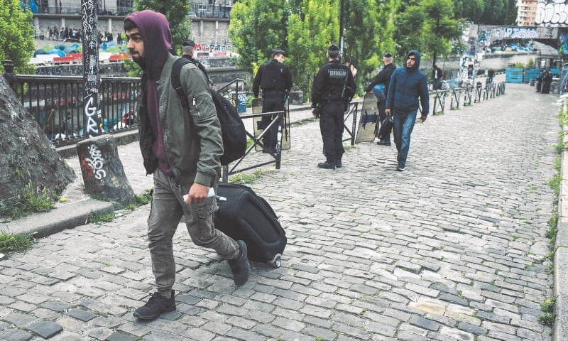PARIS: A migrant carries his belongings on Monday during an evacuation by police of the makeshift camp along the Canal de Saint-Martin on Monday.—AFP