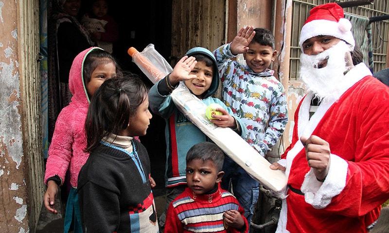 لاہور کی جوزف کالونی میں سانتا کلاز بچوں میں تحائف تقسیم کر رہا ہے — فوٹو عمار شریف