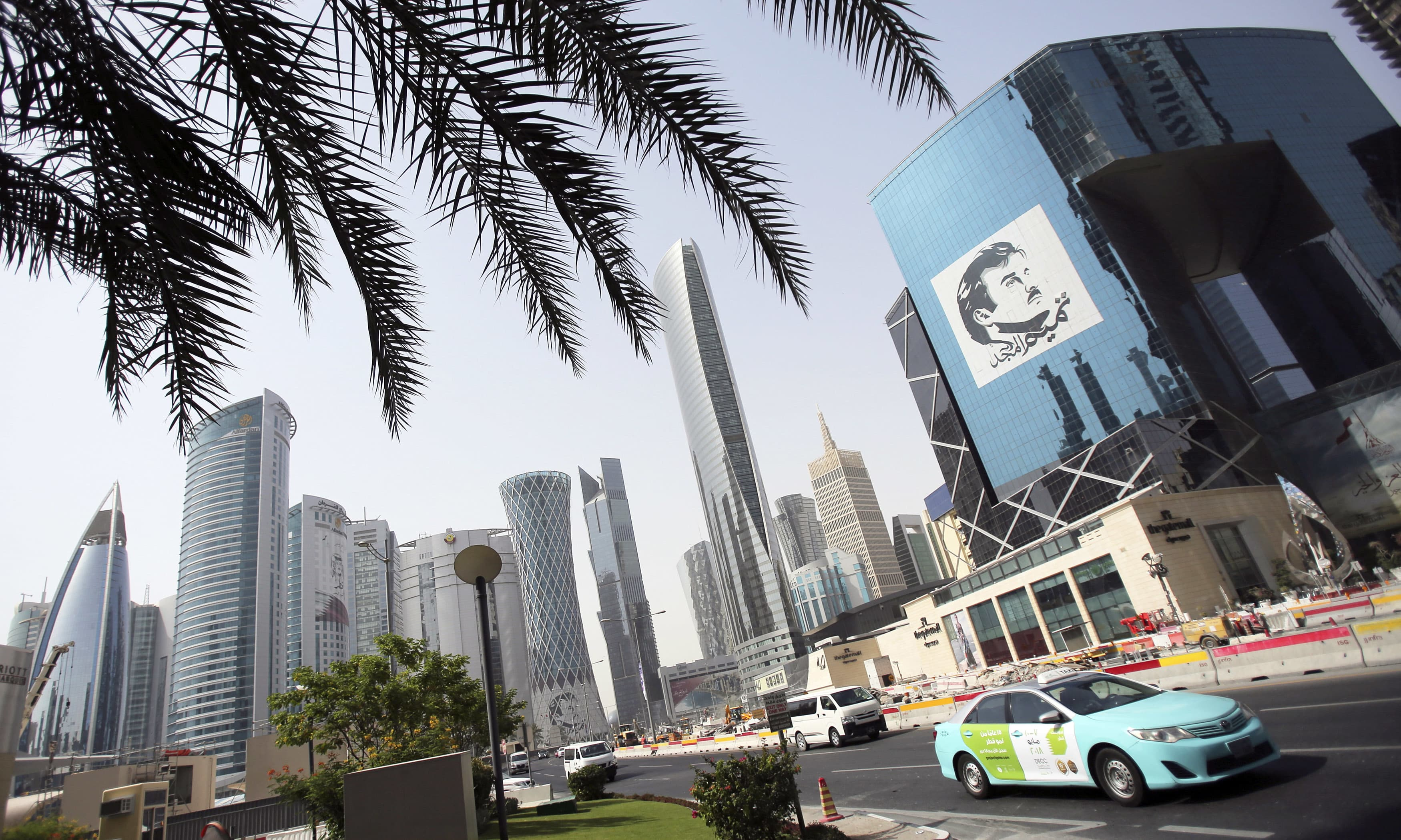 A taxi passes by a building with the image of the Emir of Qatar, Sheikh Tamim bin Hamad Al Thani, in Doha. —AP