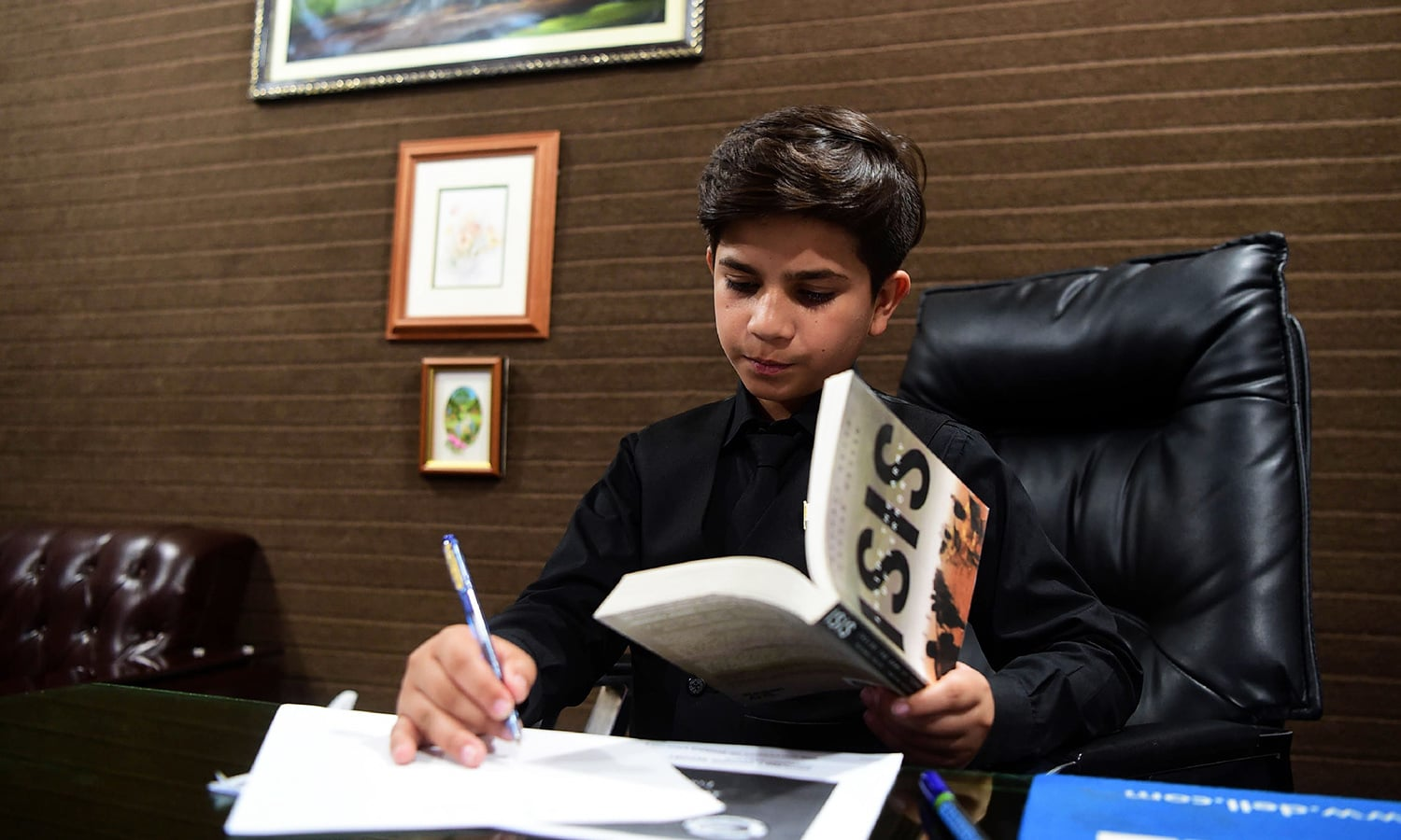 Hammad Safi takes notes at a languages academy in Peshawar. — AFP