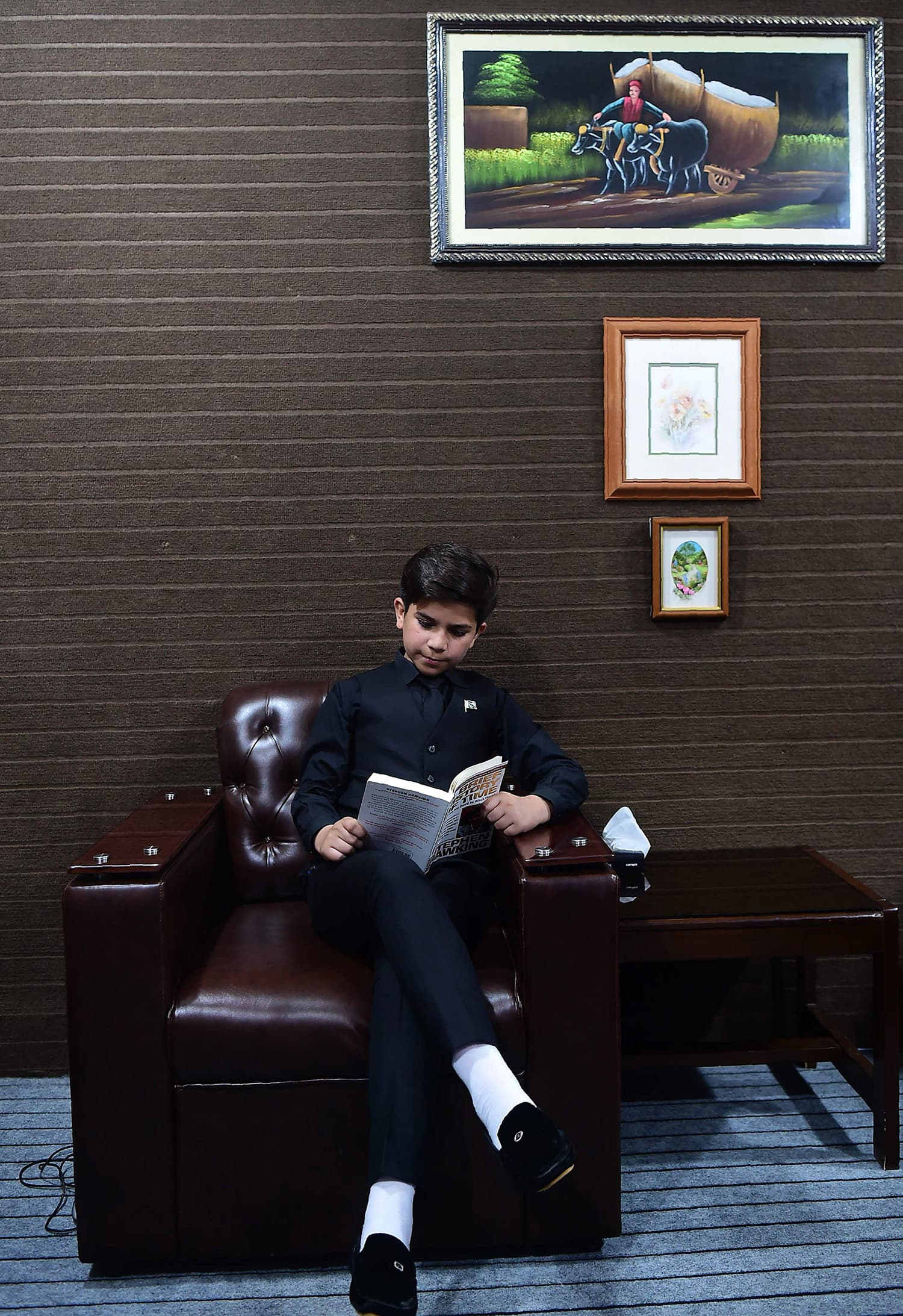 Hammad Safi reads a book at a languages academy in Peshawar. — AFP