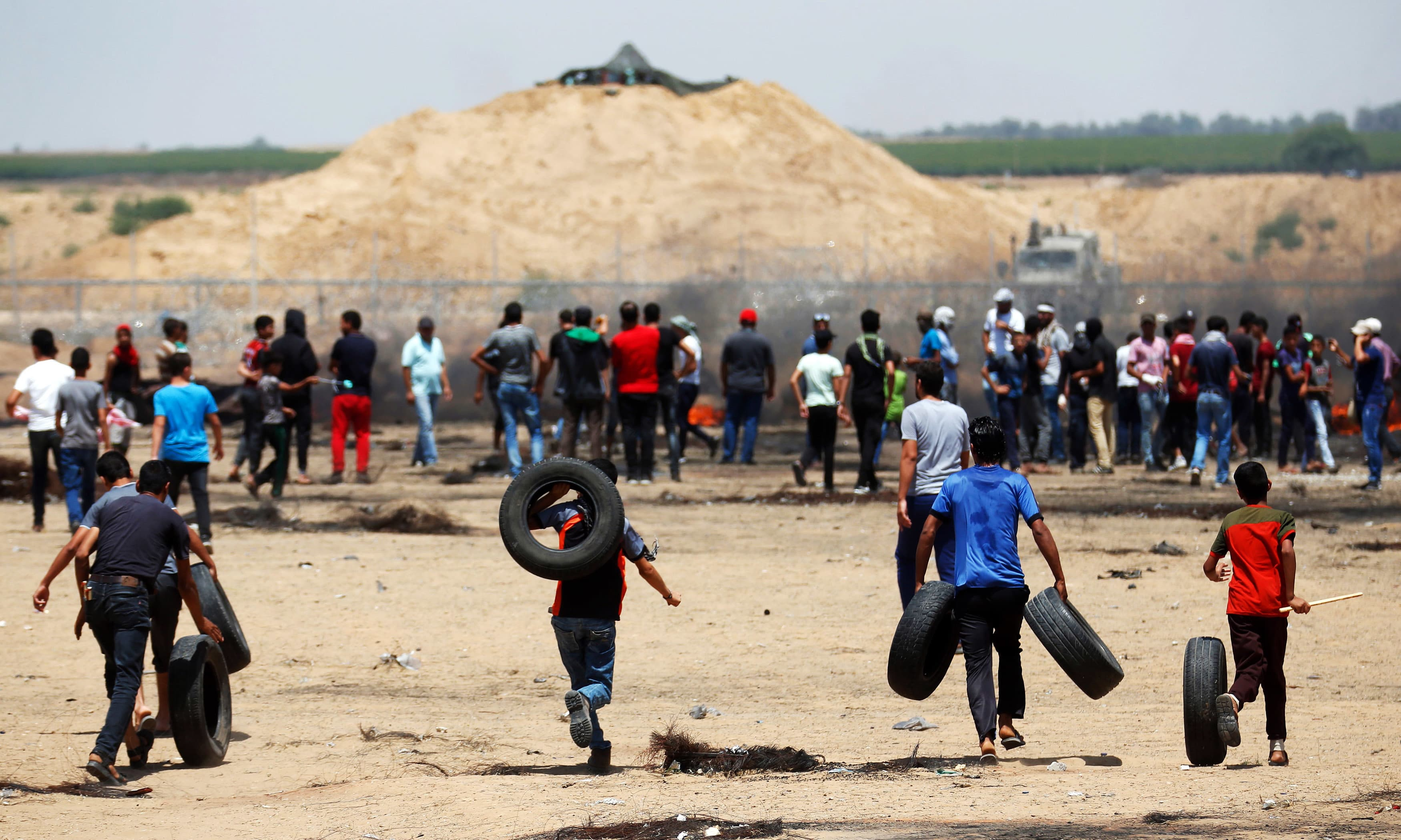 Youths carry tires on their shoulders as they head to join other protesters gathered along the border fence with Israel. —AFP