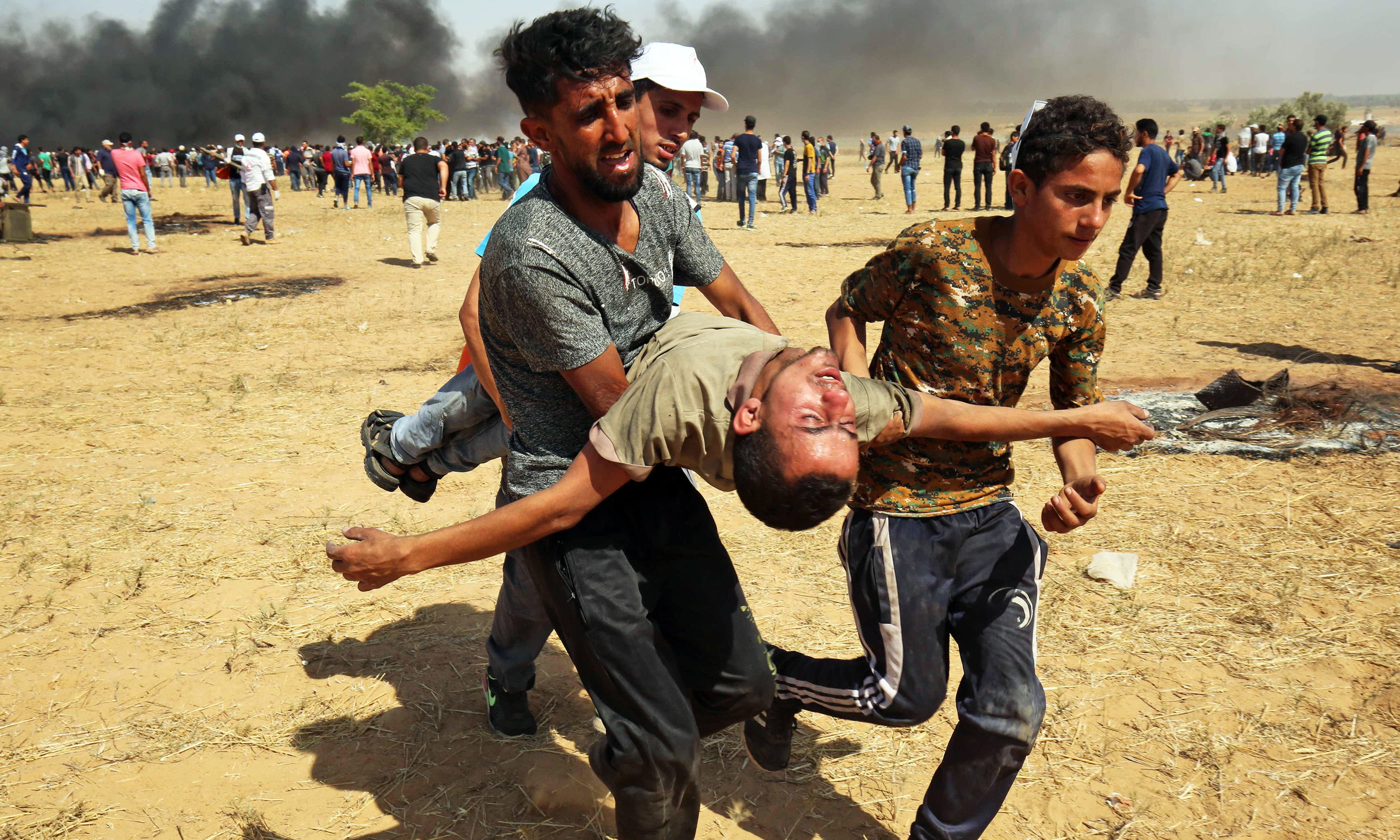 Protesters carry an injured demonstrator away from the scene of clashes with Israeli forces. —AFP