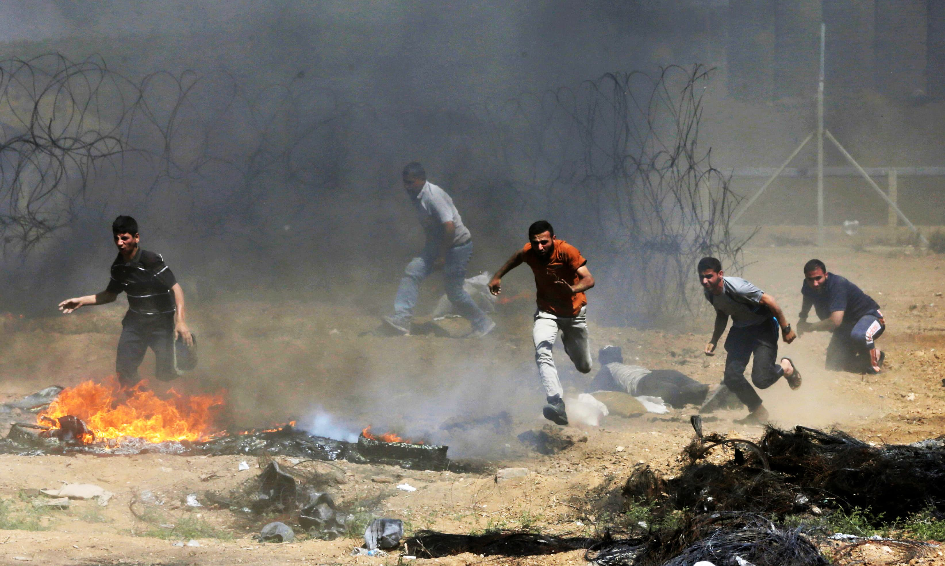 Palestinian protesters run for cover as smoke billows from burning tyres. —AFP