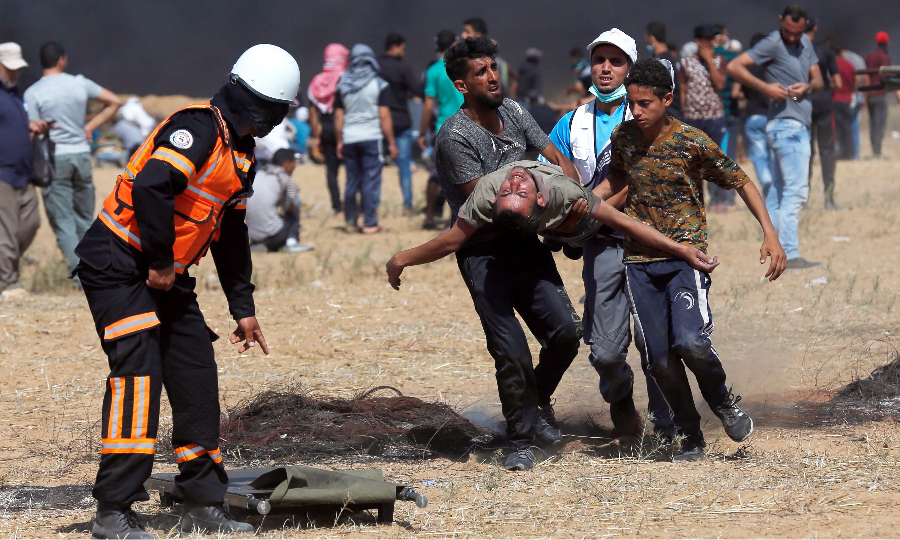 Palestinian protesters and paramedics carry an injured demonstrator away from the scene of clashes with Israeli forces. —AFP