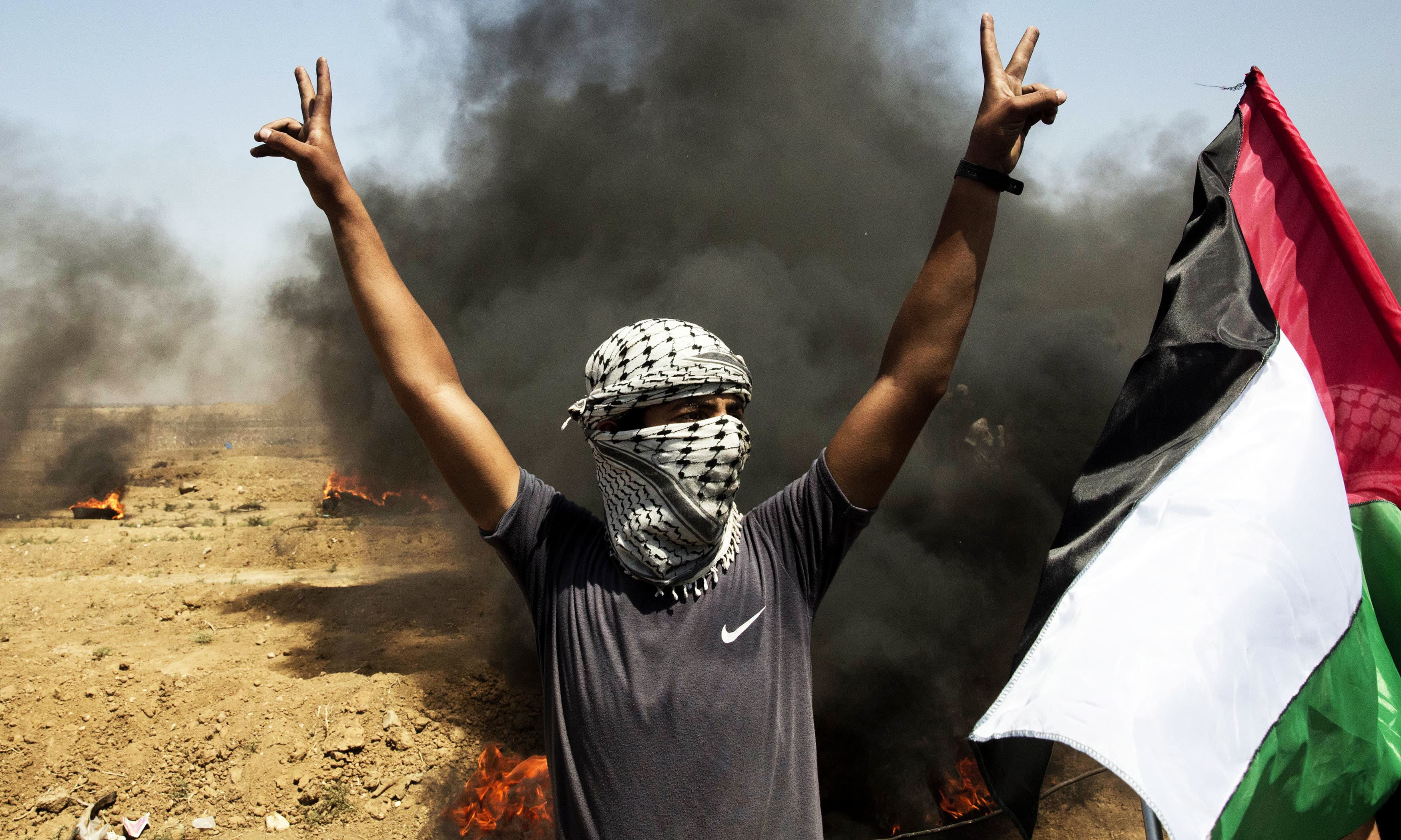 A Palestinian protester flashes victory signs while standing next to burning tires during a protest at the Gaza Strip's border with Israel. —AP