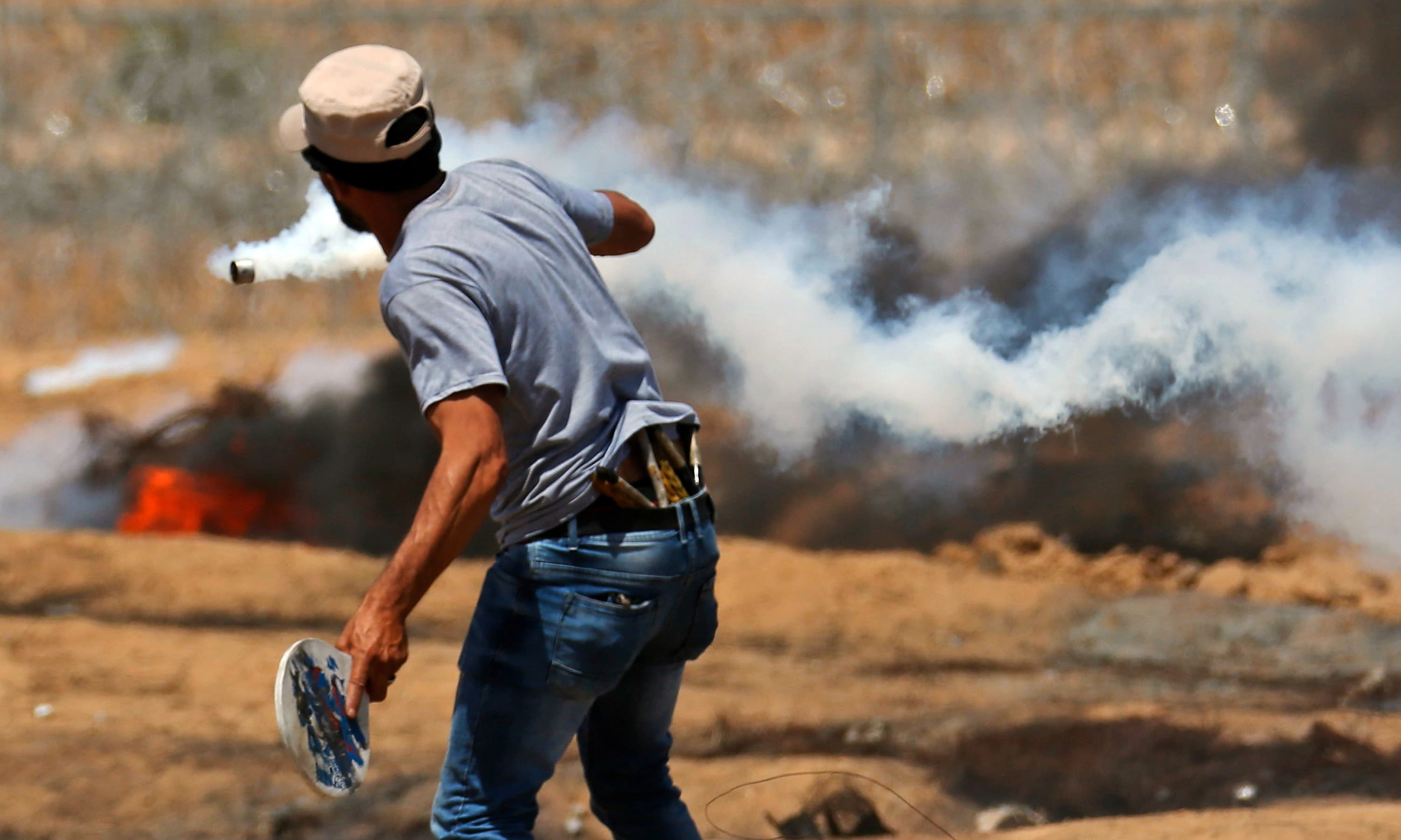 A protester uses a racket to hit back a tear gas canister across a barbed-wire fence during clashes with Israeli forces. —AFP