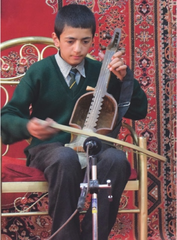 A student plays the ghazek, an indigenous string instrument