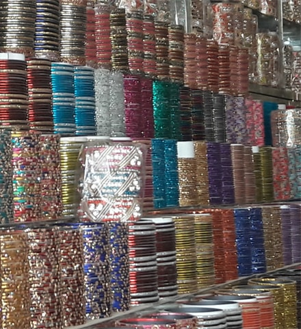 An array of colourful glass bangles decorated with gold and glitter finish displayed at a shop in Mehmoodabad
