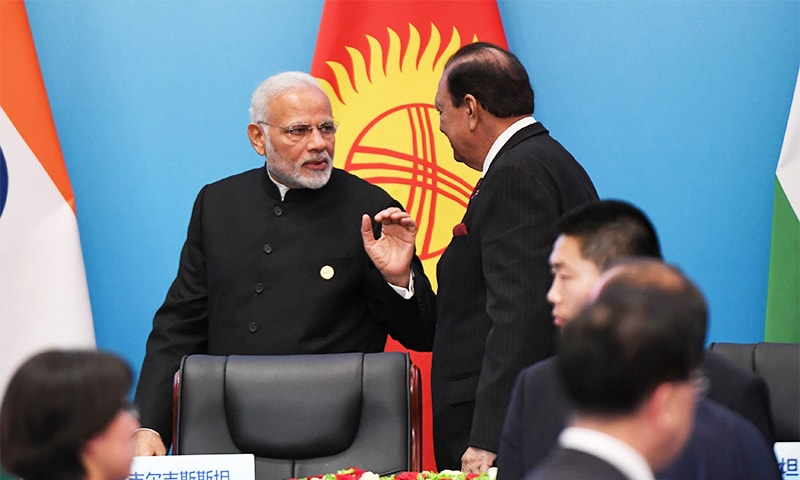 Indian Prime Minister Narendra Modi (L) talks with President Mamnoon Hussain after a signing ceremony during the SCO Summit. ─ AFP