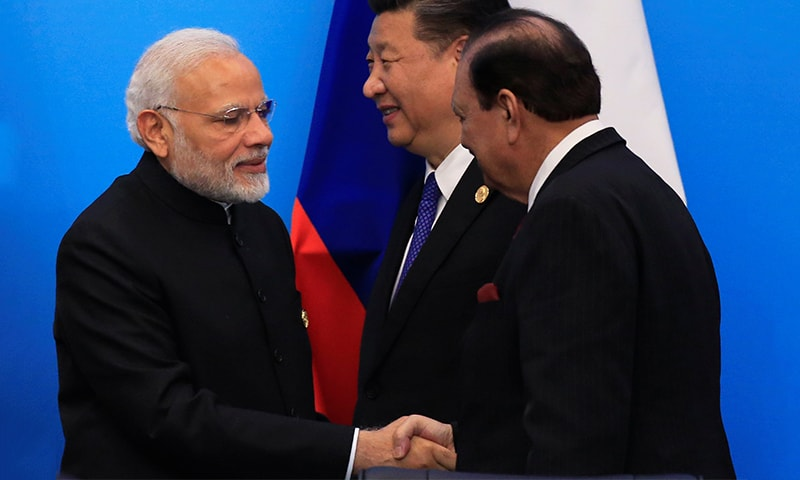 President Mamnoon Hussain shakes hands with Indian Prime Minister Narendra Modi as China's President Xi Jinping walks behind them at a signing ceremony during the Shanghai Cooperation Organization (SCO) summit in Qingdao. ─ Reuters