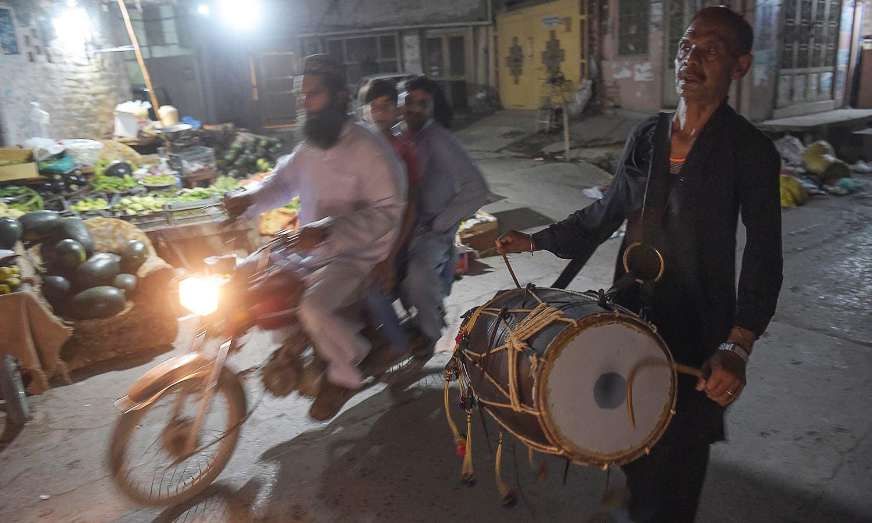 ایسے ہی ڈھولچیوں میں راولپنڈی کا لال حسین بھی ہے، وہ ہر رمضان کے مہینے میں آدھی رات کے بعد ایک بجے اپنے ڈھول پر لوگوں کو اٹھانے کا سلسلہ شروع کیا کرتا تھا — فوٹو:اے ایف پی