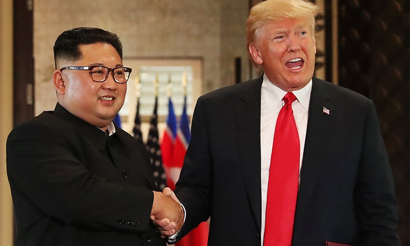 US President Donald Trump and North Korea's leader Kim Jong Un shake hands after signing documents during a summit at the Capella Hotel on the resort island of Sentosa, Singapore. ─ Reuters