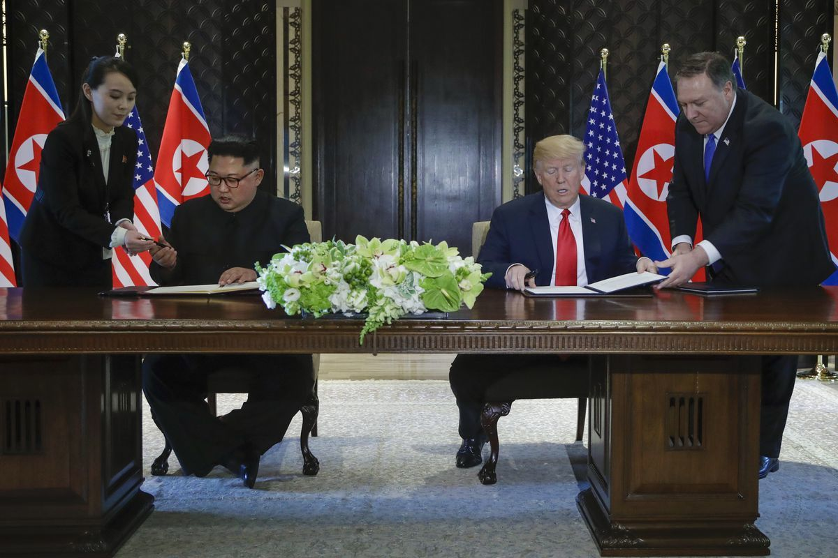 Trump and Kim Jong Un prepare to sign a document at a ceremony in Singapore on Tuesday. ─ AP