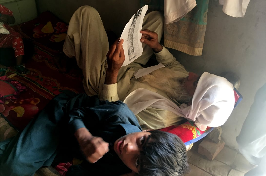 Asghar Ali reads a clipping from an Urdu language newspaper that declared his son dead in July 2014 | Subuk Hasnain