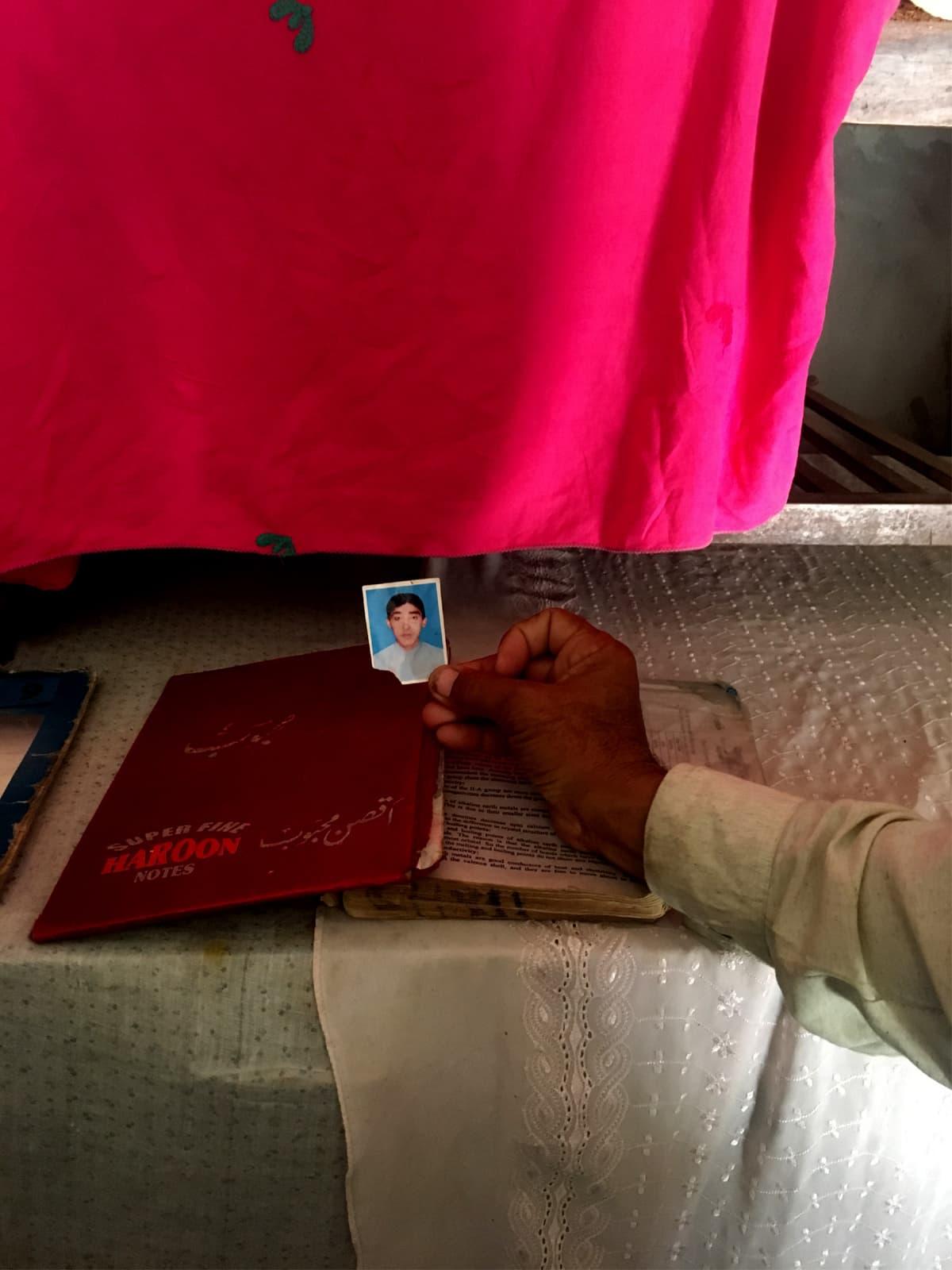 Asghar Ali holds a photo of his son, Aqsan Mehboob, in Okara this year | Subuk Hasnain