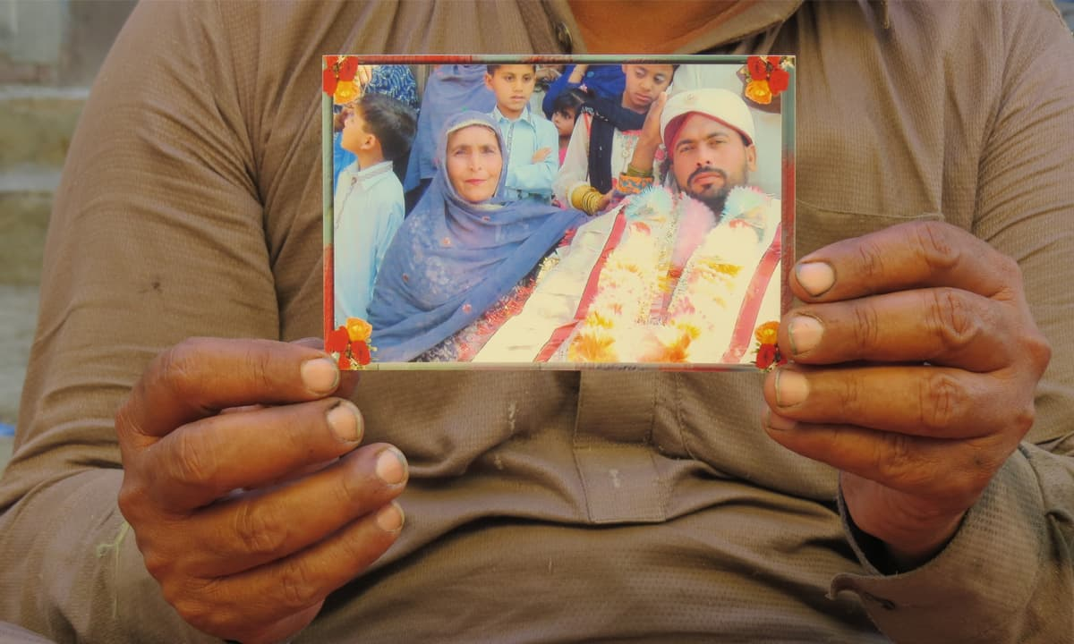 Abdul Ghafoor holds a picture of his late wife Shameem who died of  hepatitis C