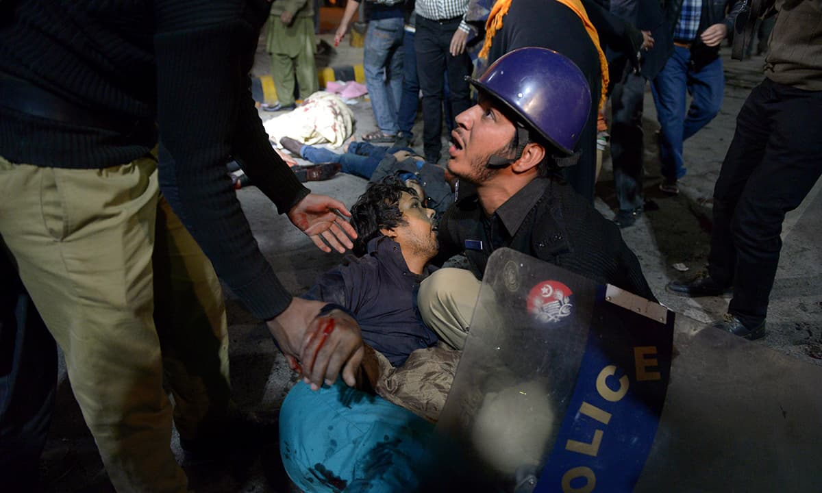 A policeman helps an injured person after a blast near the Punjab Assembly in Lahore in February 2017 | Murtaza Ali, White Star