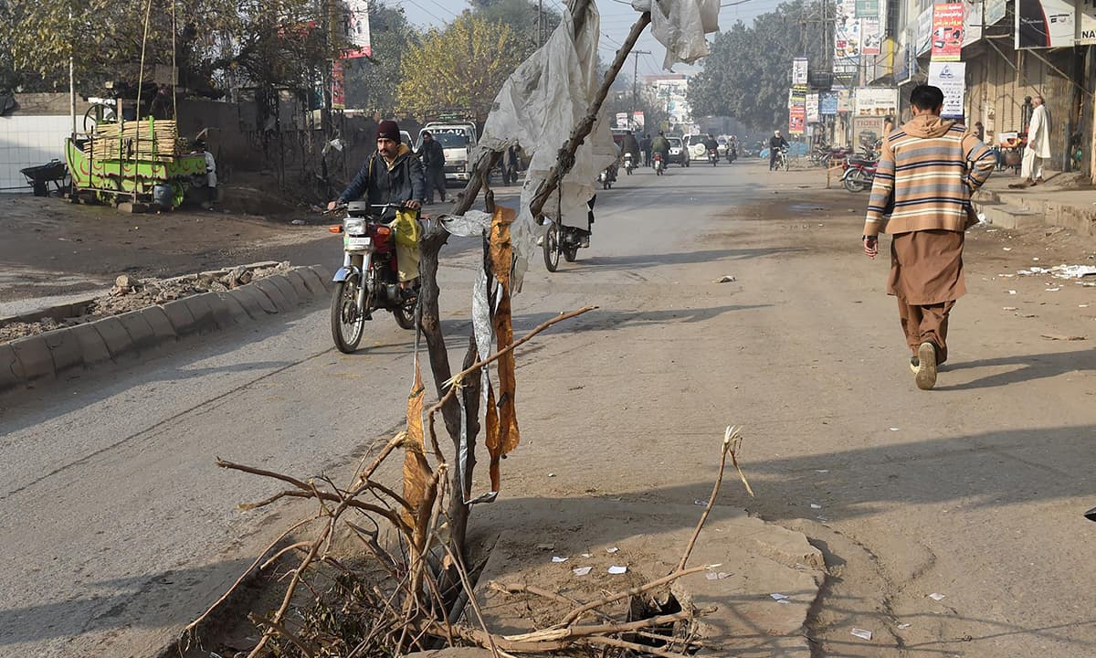Tree branches used to warn motorists to avoid an open manhole in the centre of the road near Australia Chowk, Lahore | Murtaza Ali, White Star