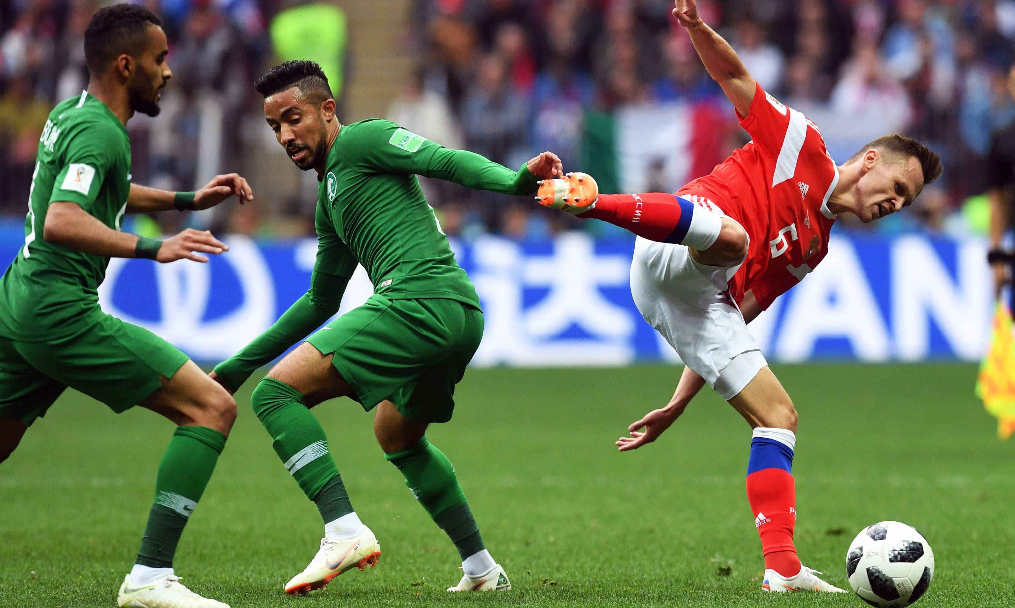 Saudi midfielder Hatan Babhir vies with Russia's midfielder Denis Cheryshev. —AFP