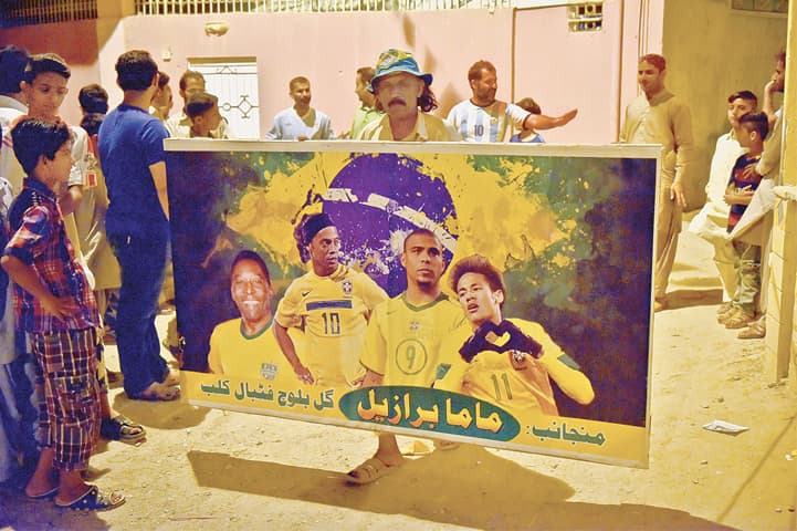 On the eve of the Fifa World Cup Russia-2018, Mama Brazil with his Panaflex poster, has stories to tell about his favourite team and players to the children of Siddiq Goth in Malir. —Photo by Fahim Siddiqi / White Star